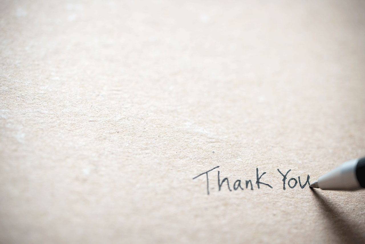 Hand_writing_thank_you_on_piece_of_old_grunge_paper